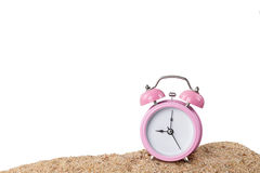 Pink alarm clock on the beach. With white background Stock Photography