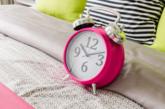 Pink alarm clock on bed Stock Photo