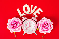Pink alarm clock  with love wooden word. Royalty Free Stock Photography