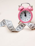 Pink alarm clock and measuring tape Royalty Free Stock Images