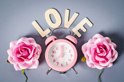 Pink alarm clock and pink rose with love word. Royalty Free Stock Images
