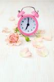 Pink alarm clock, rose and petals Royalty Free Stock Photos
