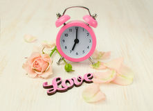 Pink alarm clock, rose, petals and the word Stock Image