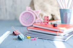Pink alarm clock and stationery for school. Light colors, space for text. royalty free stock image