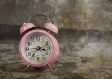 Pink alarm clock with vintage background Royalty Free Stock Photos