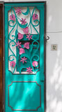 Pink and Aqua Door. An ornate door of agua metal and pink scrollwork flowers stock image