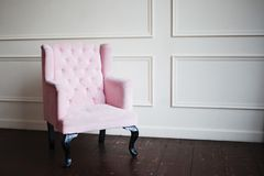 Pink armchair against wall. Perspective distortion and free space. Pink armchair against the wall. Perspective distortion and free space Stock Photos