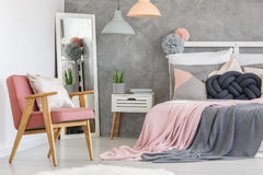 Pink armchair and mirror. Pink armchair with decorative cushion and big mirror in the bedroom corner Royalty Free Stock Images