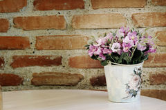 Pink artificial flower on cement brick wall Stock Images