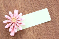 Pink artificial flowers and note paper stuck on dark wood. Royalty Free Stock Images