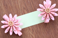 Pink artificial flowers and note paper stuck on dark wood. Stock Photos