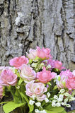 Pink artificial rose bouquet over tree trunk Stock Image