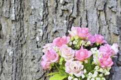 Pink artificial rose bouquet with tree trunk background Stock Image