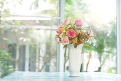 Pink artificial roses in ceramic vase near window Royalty Free Stock Image