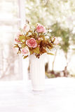 Pink artificial roses in ceramic vase near window Stock Photo