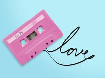Pink audio cassette tape with label tag love song tangled tape. Ribbon word love isolated on blue background, top view stock photography