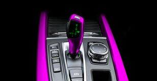 Pink Automatic gear stick of a modern car. Modern car interior details. Close up view. Car detailing. Automatic transmission lever. Shift isolated on black stock illustration