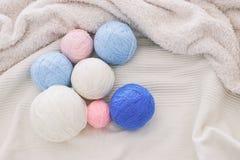 pink& x27; błękit i biel przędz piłki wełna nad miękkim łóżkiem ciepłe i wygodne fotografia stock