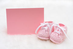 Pink Baby Booties. Baby booties with a blank card sitting on a white background royalty free stock photos