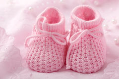 Pink baby booties. On pink background royalty free stock images