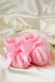 Pink Baby Booties. Pink knitted baby booties on cream satin royalty free stock photography