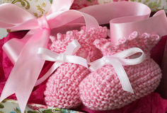 Pink Baby Booties. Pink knitted baby booties with pink ribbon gift bow royalty free stock images