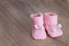 Pink baby booties on wooden surface Stock Photos
