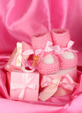 Pink baby boots, pacifier, gifts. On silk background stock images