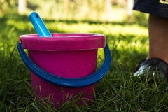Pink baby bucket and blue shovel Royalty Free Stock Photography