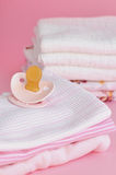 Pink Baby Clothes. Pacifier and a pile of pink baby clothes with cotton diapers in the background royalty free stock photo