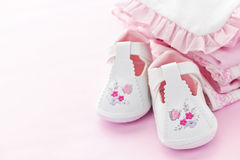 Pink baby clothes for infant girl. Infant girl clothing and shoes for baby shower on pink background Royalty Free Stock Images