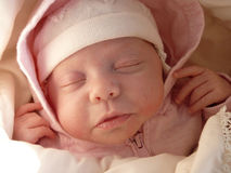 Pink baby girl. Dreaming sweet baby girl in knitted bonnet and pink hood Stock Image