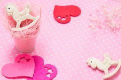 Pink baby girl theme. 2 rocking pony toys in pink small bucket and felt hearts flat lay. Top view. Copyspace stock images