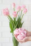 Pink baby`s bootees and pink tulips Royalty Free Stock Image