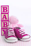 Pink baby shoes. Pink denim baby shoes, baby blocks and teddy bear stock photo