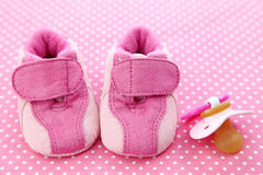 Pink baby shoes and dummy Stock Images