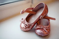 Pink baby shoes for girls. Pink baby shoes standing on the windowsill royalty free stock photography