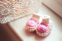 Pink baby shoes. Newborn concept. Pink baby shoes for newborn baby child at home window light. Birth concept stock images