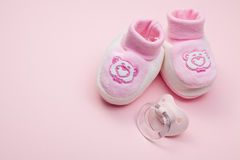Pink baby shoes and pacifier Royalty Free Stock Photos