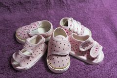 Pink baby shoes. On violet textured background stock photography