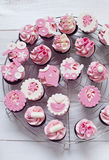 Pink baby shower cupcakes. With baby boots, strollers, feeders and flowers Stock Photos