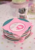 Pink baby shower napkins on plates. Pink baby shower paper napkins on plates with a jar of forks in the background Royalty Free Stock Image