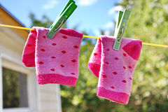 Pink baby sock hanging on the clothesline Royalty Free Stock Photos