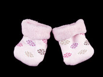 Pink baby socks on black Royalty Free Stock Images