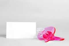 Pink baby soother. And blank greeting card stock photography