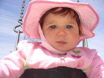 Pink Baby in a Swing. An adorable one-year old girl sits in a swing with a pink outfit and matching hat royalty free stock images