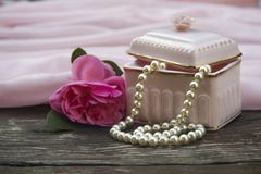 Pink background with a box and pearl beads royalty free stock image