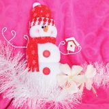 Pink background Christmas red snow white snowman soft toy with white hibiscus flowers and white tinsel. Happy snow white snowman toy with red cap and shawl Stock Photography