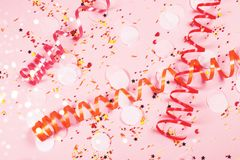 Pink background decorated with serpantine and confetti. royalty free stock images