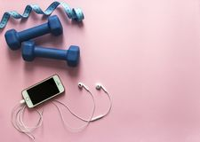 On a pink background dumbbells blue and flying centimeter figure sport headphones music phone iphone smartphone soft light royalty free stock image